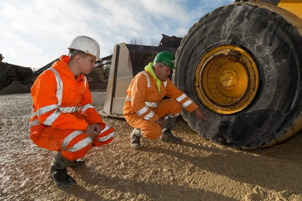 An apprentice Mineral Processing Mobile and Static Plant Operator crouching down with colleague next to mobile heavy plant vehicle